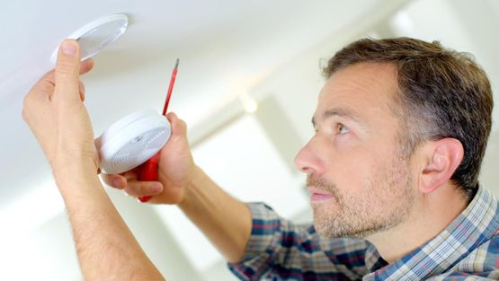 One of our team installing a carbon monoxide detector at a domestic premises